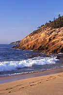 Sand Beach sits between mountains and rocky shores within Acadia National Park.